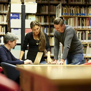 Drei Personen in einer Bibliothek