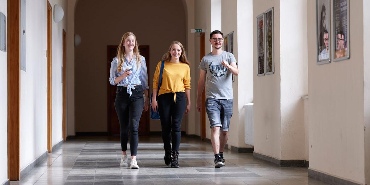 Drei FAU Studierende auf Flur