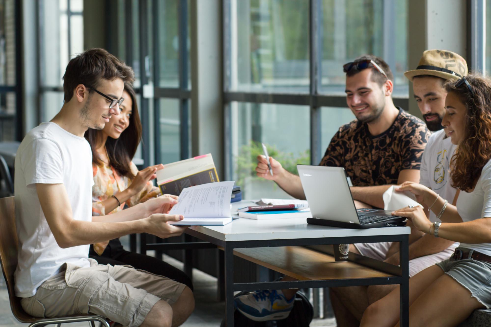 Studierende sitzen an einem Tisch und lernen gemeinsam